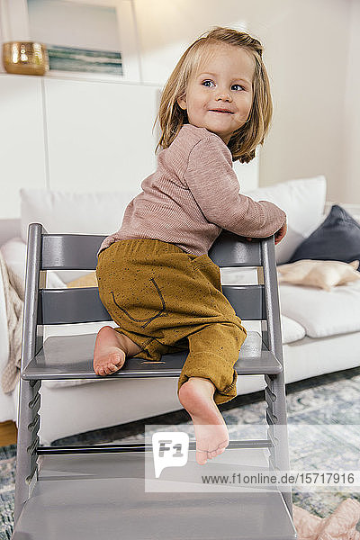 Little girl climbing on high chair at home