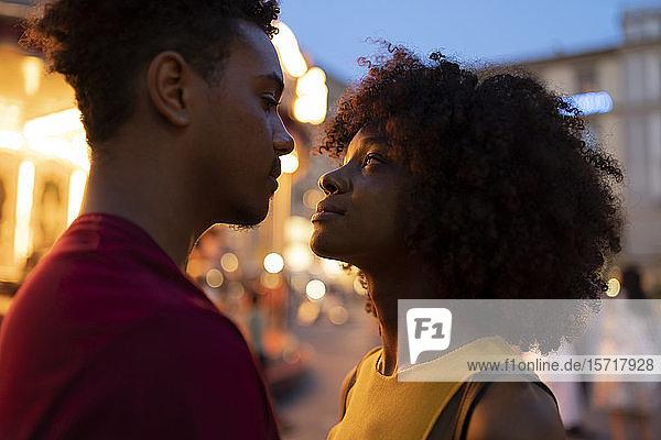 Liebevolles junges Touristenpaar an einem beleuchteten Karussell in der Stadt in der Abenddämmerung  Florenz  Italien