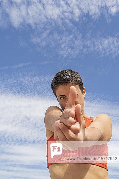 Frau macht schießende Geste mit der Hand vor dem Himmel