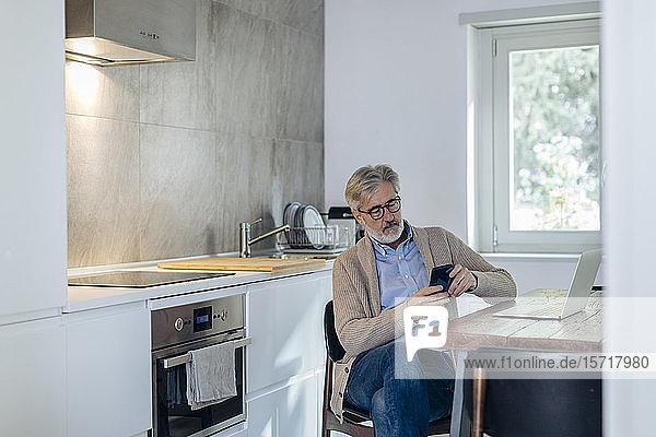 Reifer Mann benutzt Handy und Laptop in der Küche zu Hause Reifer Mann benutzt Handy und Laptop in der Küche zu Hause