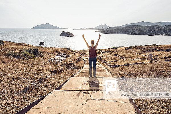 Frau am Kap Sountion stehend  mit erhobenen Armen  Rückenansicht  Attika  Griechenland
