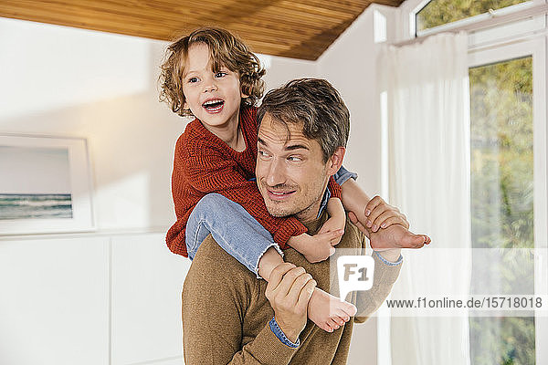 Father carrying daughter on shoulders at home
