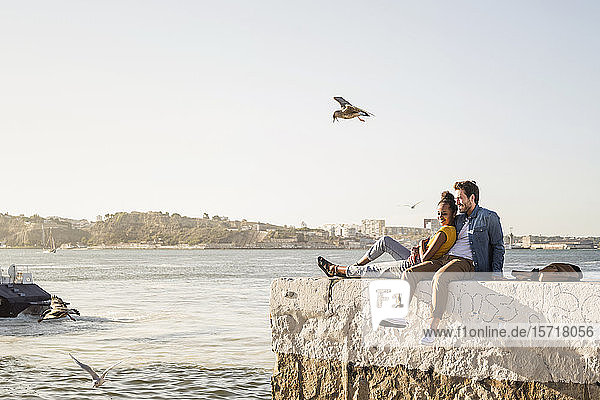 Junges Paar sitzt am Pier am Wasser und genießt die Aussicht  Lissabon  Portugal
