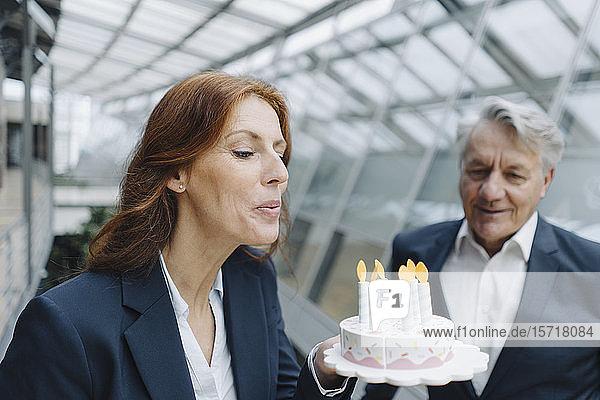 Geschäftsmann und Geschäftsfrau feiern Geburtstag im Amt mit gefälschtem Geburtstagskuchen