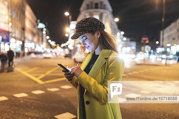 Frau mit ihrem Smartphone in der Stadt nachts neben einer Straße
