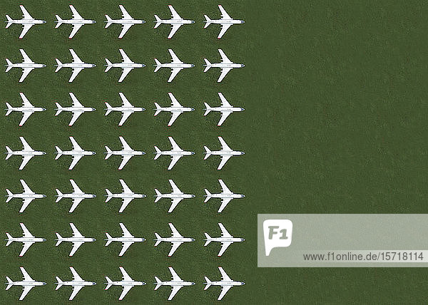 Aerial view of rows of airplanes standing on green grass