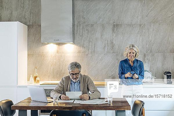 Reifer Mann mit Papieren und Laptop auf dem Küchentisch zu Hause mit Frau im Hintergrund