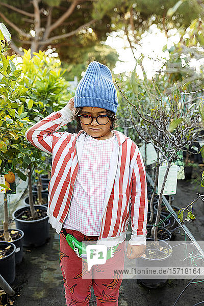 Portrait of boy at plant nursery wearing glasses and woolly hat