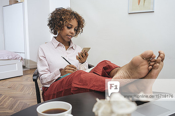 Relaxed young woman sitting at table at home using smartphone