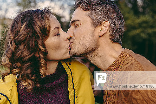 Couple kissing outdoors in autumn watched by her daughter