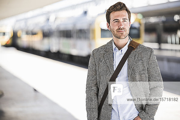 Portait of confident young businessman at the train station