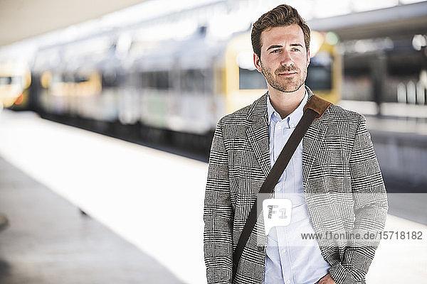 Porträt eines selbstbewussten jungen Geschäftsmannes am Bahnhof