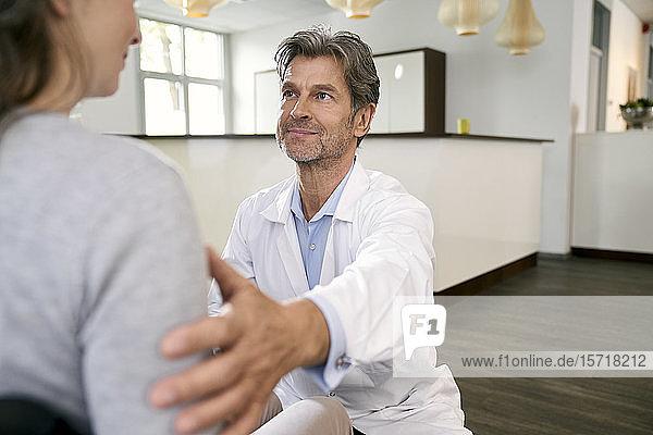 Arzt kümmert sich um Patientin im Rollstuhl