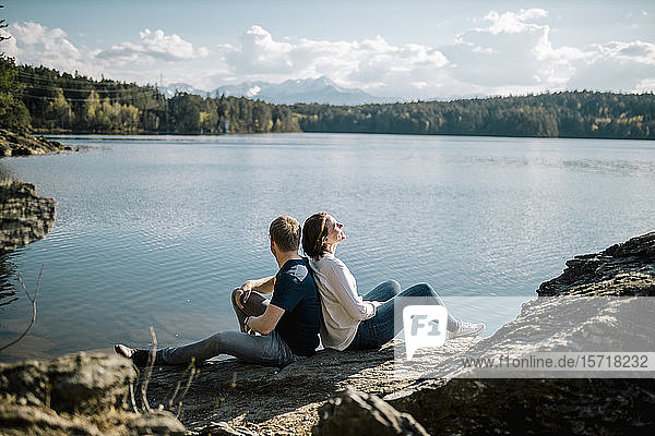 Happy couple sitting back to back at the lakeside  Forstsee  Carinthia  Austria