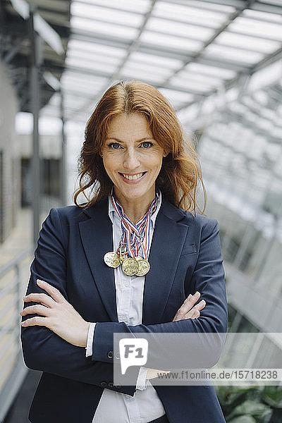 Porträt einer lächelnden Geschäftsfrau  die im Büro Medaillen um den Hals trägt