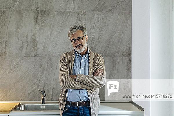 Porträt eines selbstbewussten reifen Mannes in der heimischen Küche Porträt eines selbstbewussten reifen Mannes in der heimischen Küche