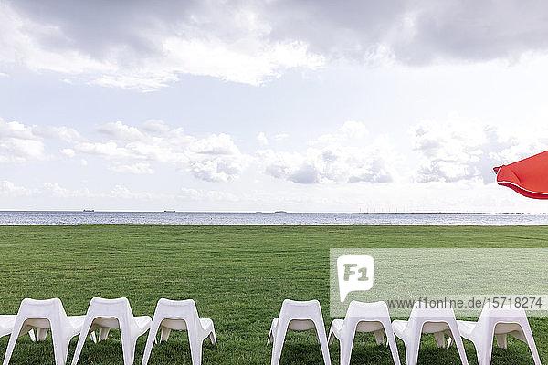 Dänemark  Charlottenlund  Weiße leere Stühle auf grünem Rasen mit der Öresund-Enge im Hintergrund