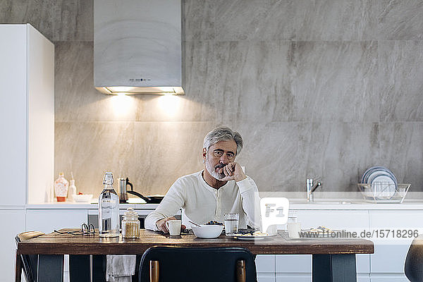 Portrait of mature man sitting at table in kitchen at home