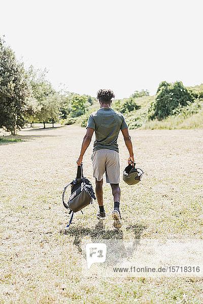 Rückansicht eines jungen Mannes mit Helm und Rucksack beim Spaziergang im Park