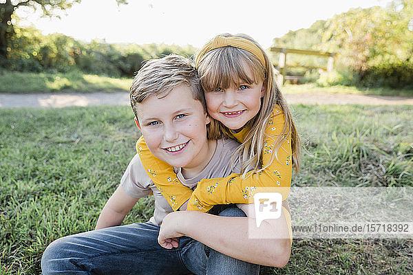 Porträt eines lächelnden kleinen Mädchens Kopf an Kopf mit ihrem älteren Bruder auf einer Wiese