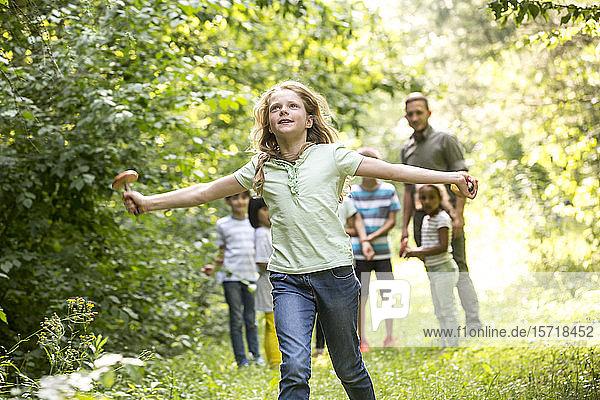 Schulkinder  die mit ihrem Lehrer im Wald spazieren gehen  Mädchen rennt  hält Pilz