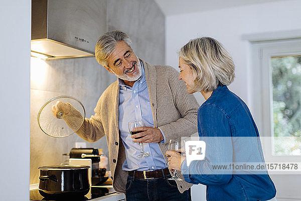Reifere Paare bereiten das Abendessen zu Hause in der Küche zu
