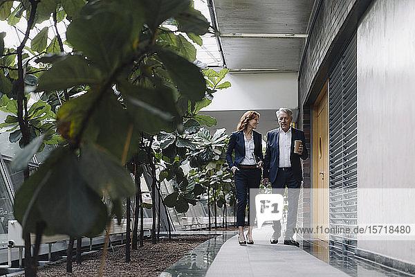 Geschäftsmann und Geschäftsfrau gehen und sprechen in modernem Bürogebäude