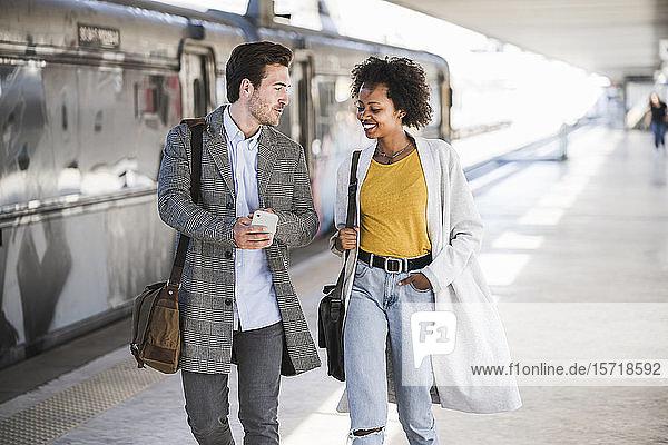 Junger Geschäftsmann und junge Geschäftsfrau beim Gehen und Sprechen am Bahnhof