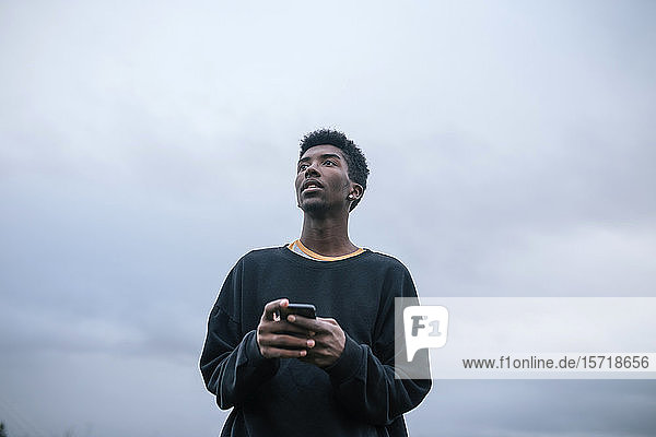 Teenager using his smartphone  low angle view