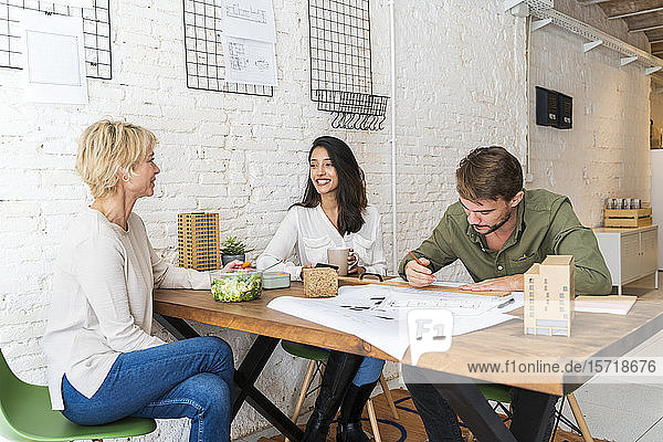 Three colleagues sharing desk in architect's office