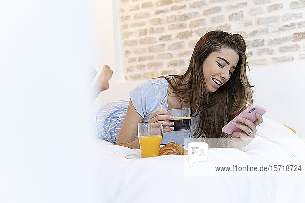 Young woman sitting on bed and using smartphone