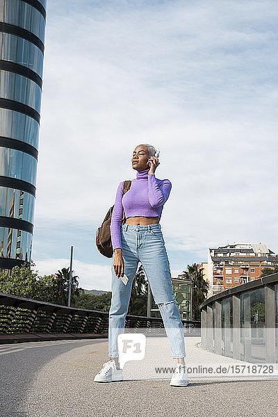Porträt einer weißhaarigen Frau mit weißen Kopfhörern  die in der Stadt Musik hört