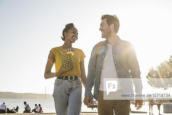 Glückliches junges Paar beim Spaziergang am Wasser bei Sonnenuntergang  Lissabon  Portugal