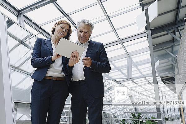 Lächelnder Geschäftsmann und Geschäftsfrau mit Tablett in modernem Bürogebäude