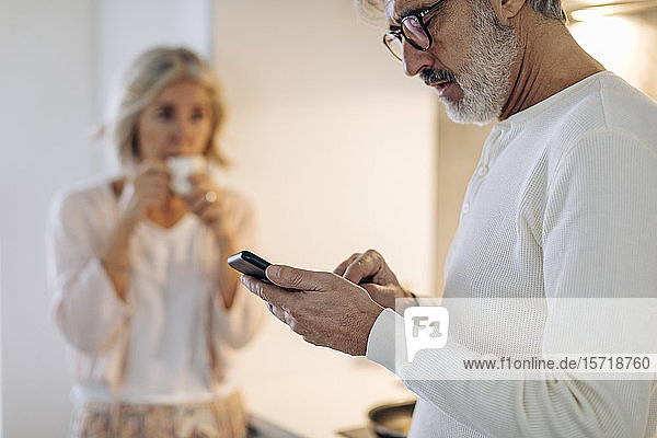 Mature man with wife using cell phone in kitchen at home