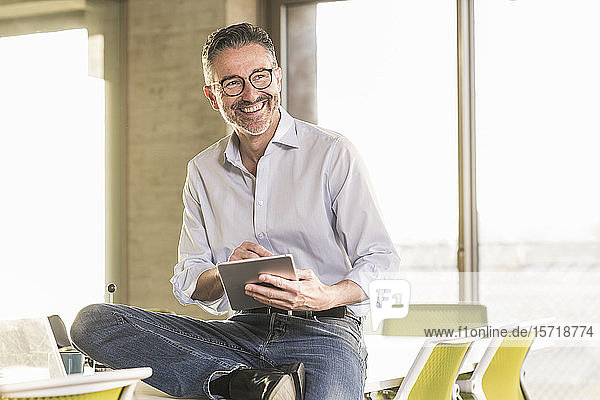 Happy mature businessman with tablet in office