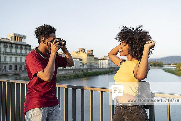 Junger Mann fotografiert seine Freundin auf einer Brücke über dem Arno bei Sonnenuntergang  Florenz  Italien