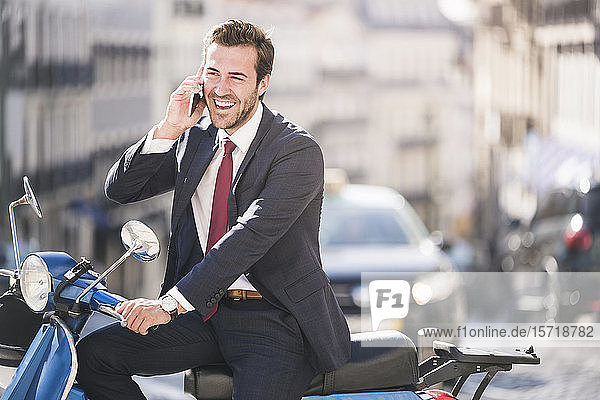 Laughing young businessman with motor scooter talking on the phone in the city  Lisbon  Portugal