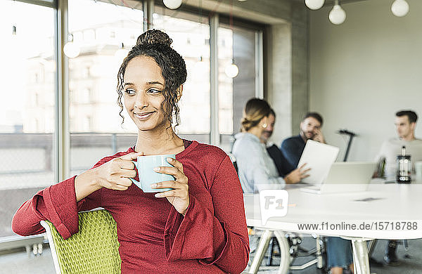 Smiling young businesswoman having a coffee break during a meeting in office
