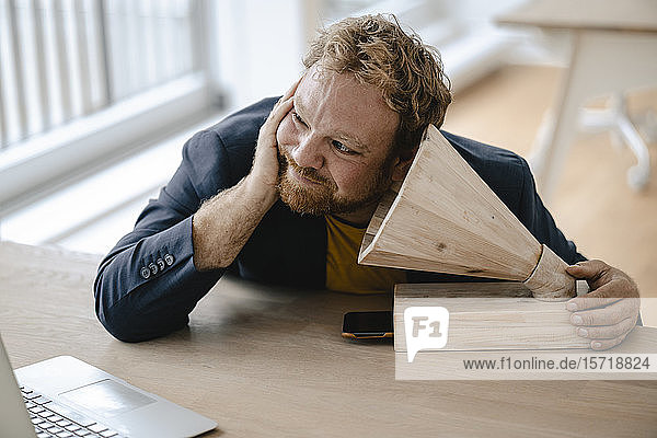 Businessman leaning on desk in office listening to music with a wooden gramophone