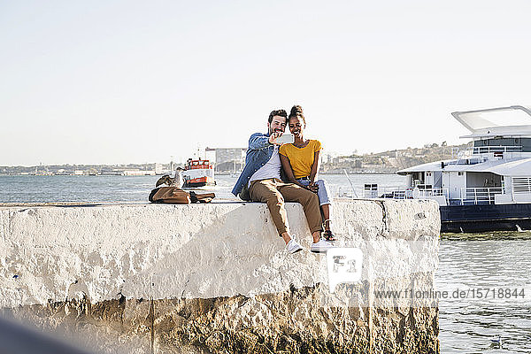 Happy young couple sitting on pier at the waterfront taking a selfie  Lisbon  Portugal