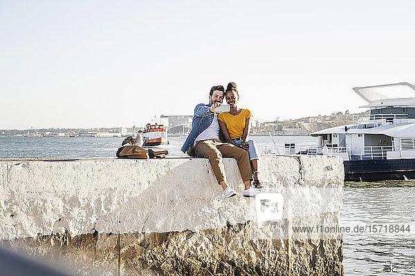 Glückliches junges Paar sitzt auf dem Pier am Wasser und macht einen Egoisten  Lissabon  Portugal