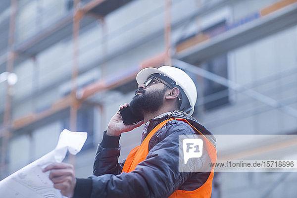 Bauingenieur am Telefon auf der Baustelle
