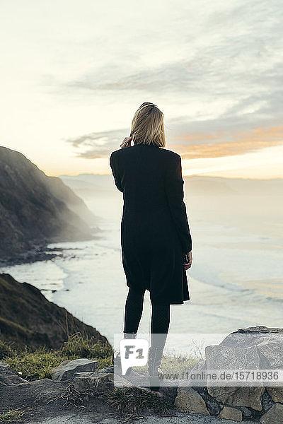 Rückansicht einer jungen blonden Frau mit Smartphone an der Küste bei Sonnenuntergang