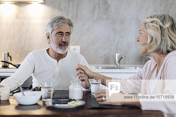 Liebevolles reifes Paar  das zu Hause in der Küche am Tisch sitzt und frühstückt