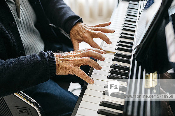 Crop view of senior man playing piano
