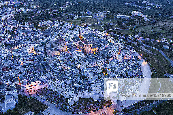Italy  Province of Brindisi  Ostuni  Aerial view of old town citadel surrounded by white houses at dusk
