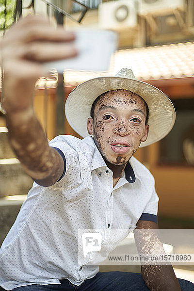 Junger Mann mit Vitiligo  der ein Smartphone benutzt und ein Selfie nimmt