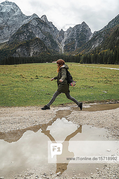 Female hiker jumping over puddle  Friuli Venezia Giulia  Italy