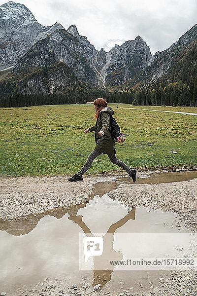 Wanderin springt über Pfütze  Friaul-Julisch Venetien  Italien